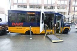 DART bus parked at a curb with doors open and ramp deployed.
