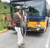 Turn bike at a 90-degree angle to rack (parallel with curb), with rear wheel closest to bus.