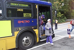 Photo of woman stepping off special Husky football service bus.